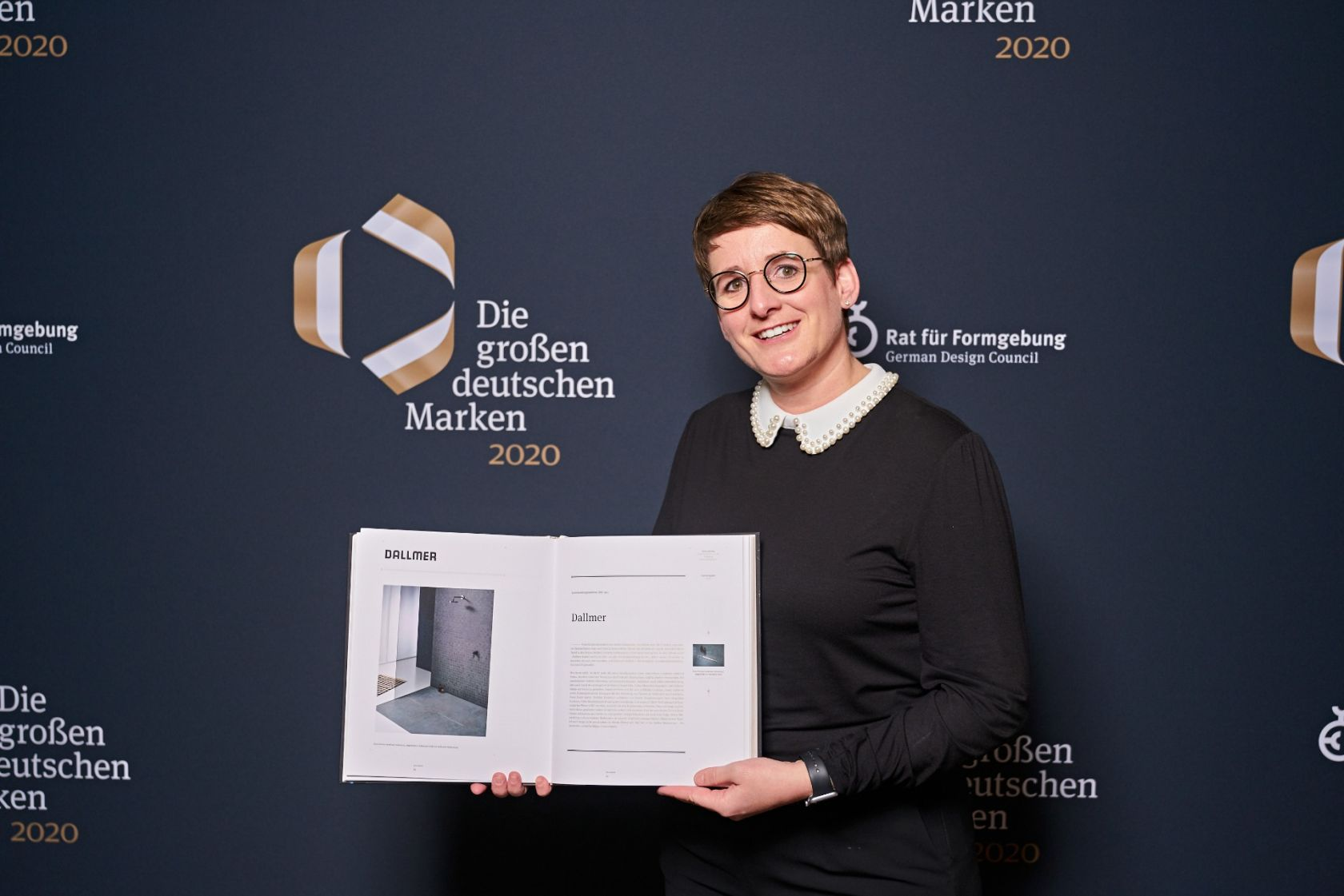 Recently, the seventh edition of the book 'The Major German Brands' was presented in Berlin. Yvonne Dallmer, Managing Director of Dallmer GmbH + Co. KG, proudly shows off her company's mention in the publication of the German Design Council. (Photo:  German Design Council / photography:Martin Diepold, Grand Visions)